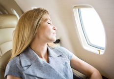 Businesswoman Sleeping In Private Jet Stock Images