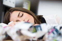 Businesswoman sleeping on the table with trash papers Royalty Free Stock Photos