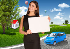 Businesswoman with small car, houses and trees Royalty Free Stock Image