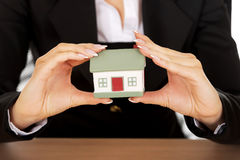 Businesswoman with small house behind the desk Stock Photos