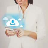 Businesswoman with smart phone downloading from cloud Stock Photo