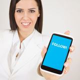 Businesswoman with smart phone that states follow Stock Image