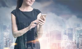 Businesswoman with a smartphone, foggy city stock images