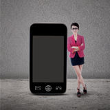 Businesswoman and smartphone on grey Royalty Free Stock Photo