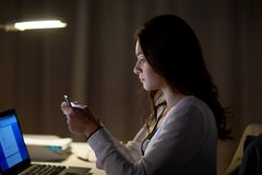 Businesswoman with smartphone at night office. Business, technology, overwork, deadline and people concept - businesswoman with smartphone at night office Royalty Free Stock Photo