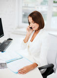 Businesswoman with smartphone in office Stock Photo