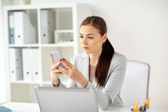 Businesswoman with smartphone at office Stock Images