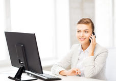 Businesswoman with smartphone in office Stock Photography