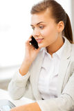 Businesswoman with smartphone in office Royalty Free Stock Photos