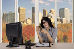 Businesswoman with smartphone in the office Stock Photos