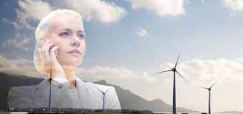 Businesswoman with smartphone over wind turbines Stock Photo