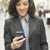 Businesswoman with smartphone, phone in focus Royalty Free Stock Photos