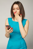 Businesswoman with smartphone receiving shocking news royalty free stock photography