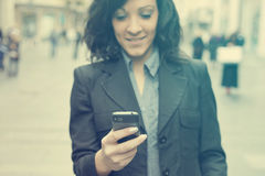 Businesswoman with smartphone walking on street. phone in focus Stock Photo