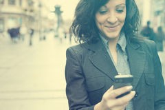 Businesswoman with smartphone walking on street Royalty Free Stock Photos