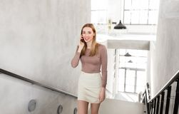 Businesswoman with smartphone walking upstairs Stock Image