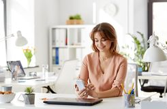 Businesswoman with smartphone working at office. Business, technology and people concept - businesswoman with smartphone working at office Stock Image