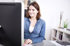Businesswoman smiling as she works at her desktop Stock Images