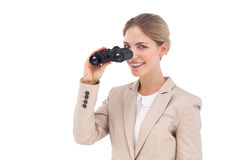 Businesswoman smiling at the camera with binoculars Stock Image