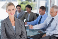 Businesswoman smiling at camera with colleagues behind Stock Photos
