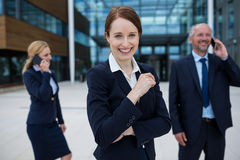 Businesswoman smiling at camera while colleagues talking on mobile phones Stock Photography