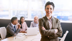 Businesswoman smiling at the camera in front of her colleagues stock images