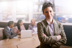 Businesswoman smiling at the camera in front of her colleagues royalty free stock photography