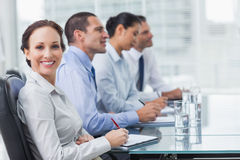 Businesswoman smiling at camera while her colleagues listening t Royalty Free Stock Images