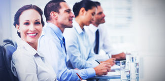 Businesswoman smiling at camera while her colleagues listening to presentation. Businesswoman in bright office smiling at camera while her colleagues listening Stock Photos