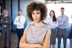 Businesswoman smiling at camera while her colleagues standing in background. Successful businesswoman smiling at camera while her colleagues standing behind him royalty free stock photo