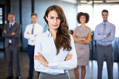 Businesswoman smiling at camera while her colleagues standing in background. Successful businesswoman smiling at camera while her colleagues standing behind him stock photography