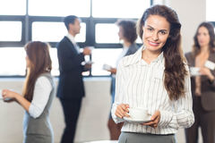 Businesswoman smiling at camera while her colleagues standing in background Royalty Free Stock Photography