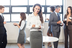 Businesswoman smiling at camera while her colleagues standing in background Royalty Free Stock Photos