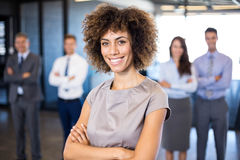 Businesswoman smiling at camera while her colleagues standing in background. Successful businesswoman smiling at camera while his colleagues standing behind him stock photography