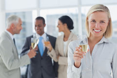 Businesswoman smiling at camera holding champagne Stock Image