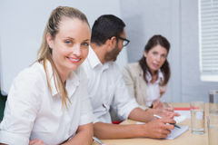 Businesswoman smiling at camera with team behind her Royalty Free Stock Image