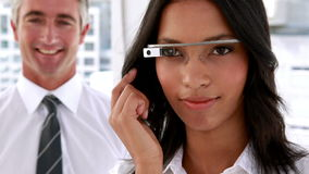 Businesswoman smiling at camera using smart glasses stock video
