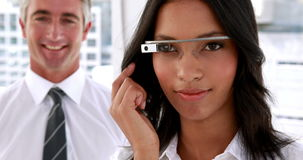 Businesswoman smiling at camera using smart glasses