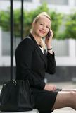 Businesswoman smiling with cellphone outdoors Royalty Free Stock Photos