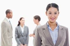Businesswoman smiling with co-workers. Close-up of a businesswoman smiling with co-workers in the background Royalty Free Stock Photo