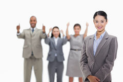 Businesswoman smiling with co-workers approving in the backgroun Stock Photos