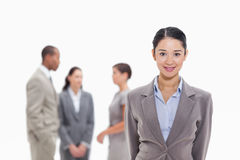 Businesswoman smiling with co-workers in the background Stock Images
