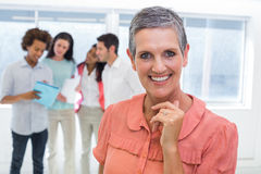 Businesswoman smiling with coworkers behind working Royalty Free Stock Photography