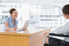 Businesswoman smiling at disabled job candidate Royalty Free Stock Image