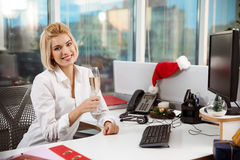 Businesswoman smiling drinking champagne sitting in office on christmas day. Stock Photos
