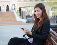 Businesswoman with smiling face sitting on bench Stock Photography