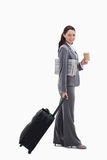 A businesswoman smiling going for a trip. Profile of a businesswoman smiling with a suitcase, a newspaper and a coffee against white background Stock Images