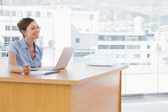 Businesswoman smiling at her desk Stock Photo