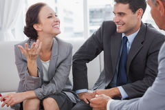Businesswoman smiling while her partners looking at her Royalty Free Stock Images