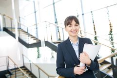 Businesswoman Smiling While Holding Documents Against Staircases stock images